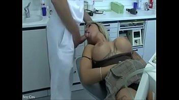 Dentista comendo a paciente na cadeira de cirurgia